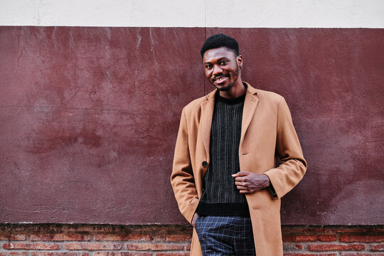 Modern glad adult black African American man wearing stylish clothes and earring looking at camera while standing against street colorful wall