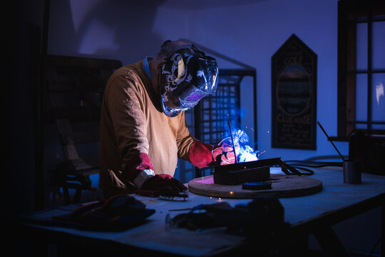 Unrecognizable male employee in protective gloves and helmet using welding machine while working in dark workshop