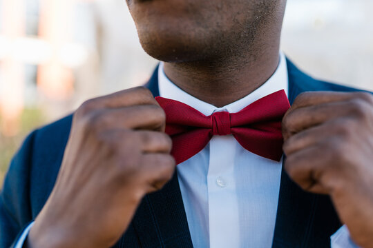 Crop unrecognizable ethnic groom in suit adjusting red bow tie on wedding day