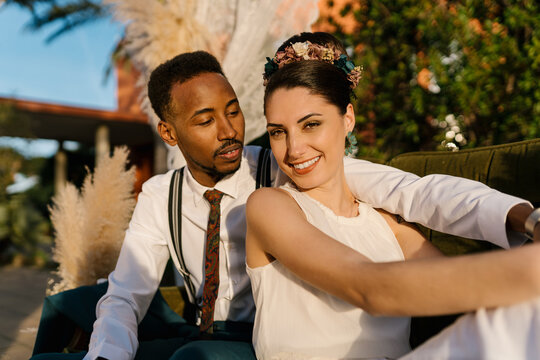 Cheerful multiracial couple of newlyweds sitting on sofa in garden and cuddling while smiling and enjoying wedding day