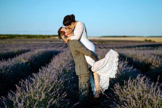 Side view of groom lifting bride while standing in lavender field on background of clear blue sky on wedding day