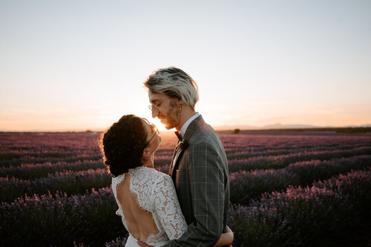 Side view of romantic newlywed couple standing face to face on spacious field against purple sunset sky