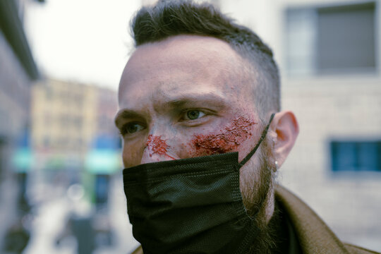 Side view hipster man with beard, cinema makeup and mask posing on the street and looking at camera