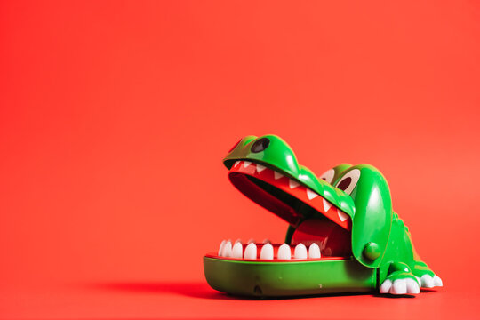 Plastic crocodile teeth toy of green color placed on table on red background in studio