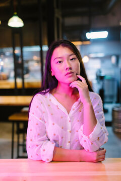 Young contemplative ethnic female touching cheek while sitting at cafeteria table with Asian food and looking at camera