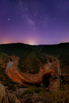 Breathtaking scenery of curved river in highlands under starry sky with sunset sun in Minas de Rio tinto in long exposure