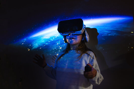 Unrecognizable young girl in casual wear and VR headset getting new experience and touching virtual object in room with colorful projector illumination