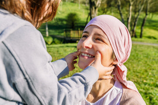 Unrecognizable daughter drawing smile with fingers on mother's face with cancer wearing pink head scarf standing on green park looking at each other