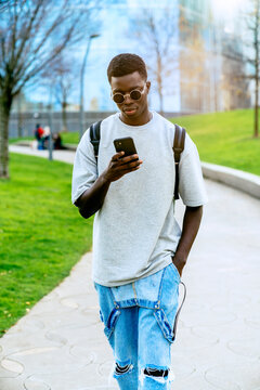 Young stylish African American male with hand in pocket surfing internet on cellphone while walking on pathway in town