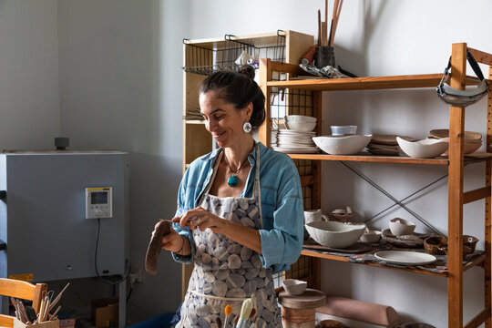 Positive adult ethnic lady in casual clothes and apron sculpting clay piece and smiling during pottery class in workshop