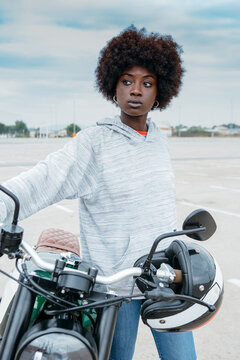 Self assured young African American woman with curly hair in stylish outfit leaning on motorbike and looking away in city outskirts