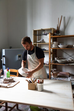 Concentrated young bearded male potter in casual clothes and apron creating white ceramic plate while working in studio