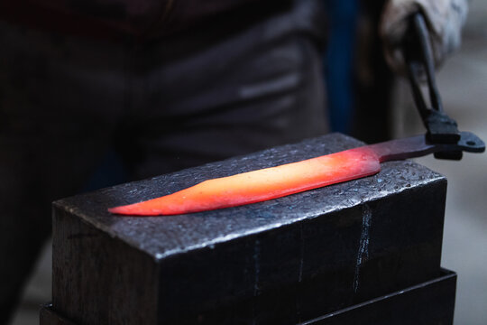 Crop anonymous blacksmith in gloves with pincers fabricating knife placed on anvil in workshop