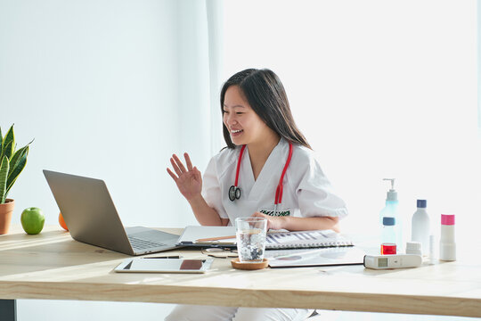 Stock photo of asian female doctor talking to a patient via video from home. The doctor is sitting in a desk with ample natural light.