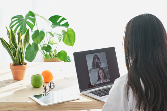 Stock photo of asian doctor talking with her ill patient via video-call.