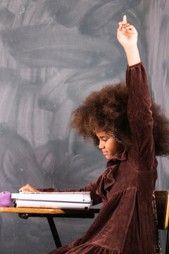 Side view of African American schoolgirl sitting with raised hand in classroom during lesson at school