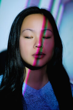 Stock photo of cool asian woman with white lights in her face closing her eyes.