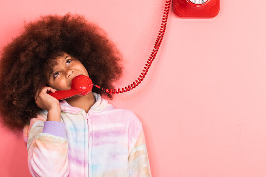 Ethnic girl with Afro hairstyle talking on old fashioned red telephone in studio and looking away on pink background