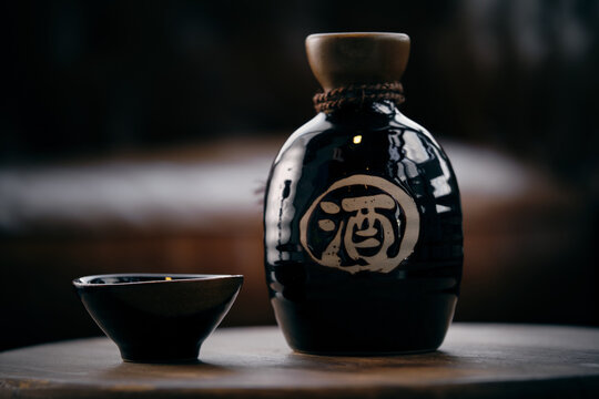Black ceramic bottle and small bowl with soy sauce placed on wooden table