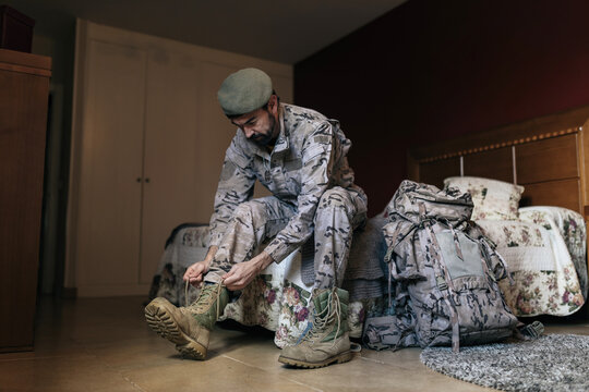 Low angle of soldier putting on boots while preparing for military service at home