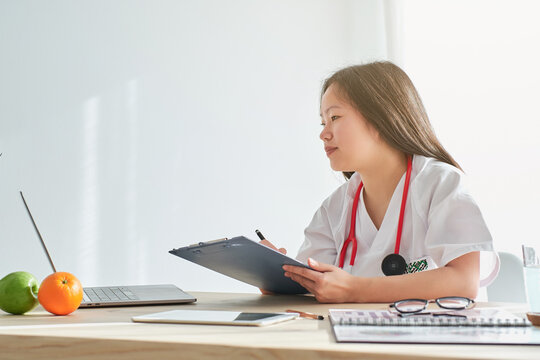 Stock photo of young female doctor taking notes in her video call with patient.