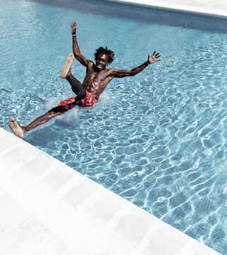 Astonished African American male in shorts falling into swimming pool