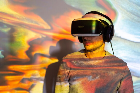 Unrecognizable young male in casual wear and VR headset getting new experience and touching virtual object in room with colorful projector illumination