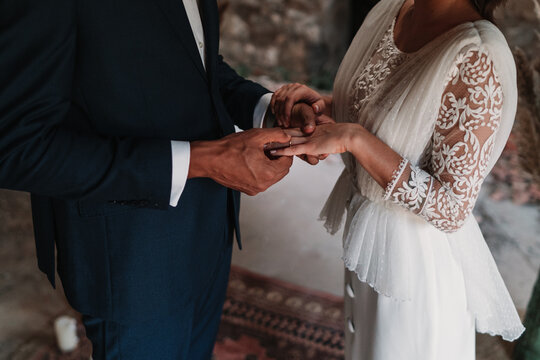 Side view of cropped unrecognizable ethnic groom putting ring on finger of bride in fancy wedding gowns holding hands gently with affection