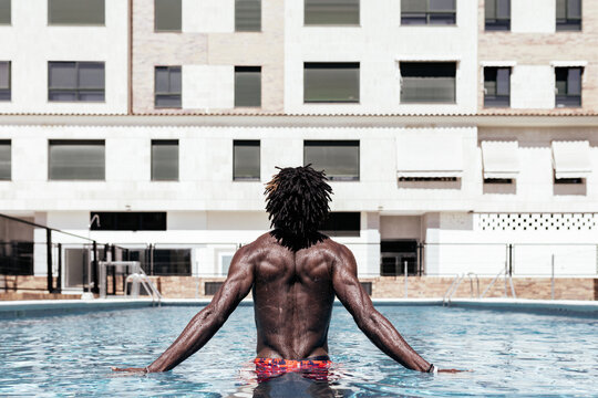 Carefree African-American man on his back in the pool and enjoying summer vacation.