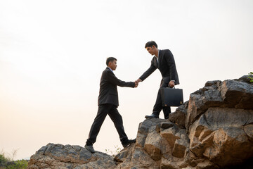 Businessman helping each other hike up a mountain at sunset back Wall mural