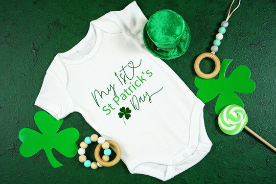 Happy St Patrick's Day baby wear onesie bodysuit, styled with leprechaun hat, shamrocks, on a textured green background. My first St Pats Day text.