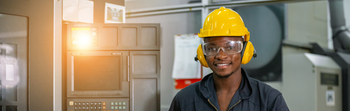 Engineering male african american workers wear soundproof headphones and yellow helmet working at operating CNC machine. work factory industrial concept.