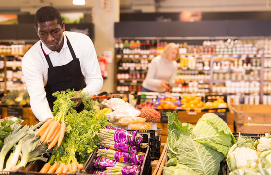 African male grocery worker in apron arranging fresh vegetables on shop counter