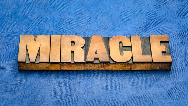 miracle word abstract in vintage letterpress wood type, a highly improbable or extraordinary event, development, or accomplishment that brings very welcome consequences