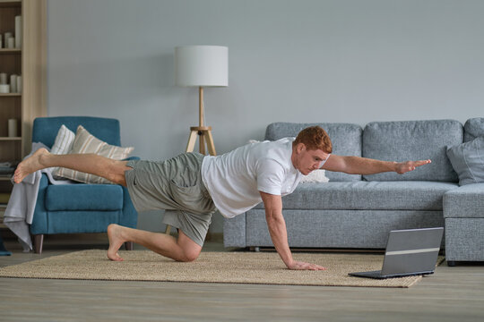 redhead man in white t-shirt works out in the living room. Man doing sports on a mat watching videos on a laptop in the living room with water and dumbbells on the floor