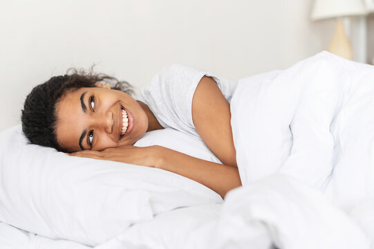 Positive young relaxed mixed-race woman covered with cozy warm soft blanket lying down and staying at home, resting head on the pillow and daydreaming, napping, looking away, enjoying day off in bed