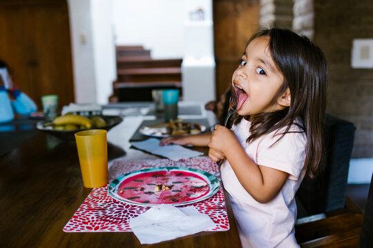 little girl child having breakfast in home in Mexico city
