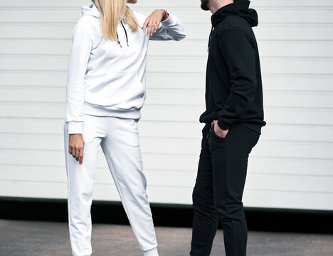 Woman wears white hoodie and man wears black hoodie. Clothing mockup. Streetwear design template