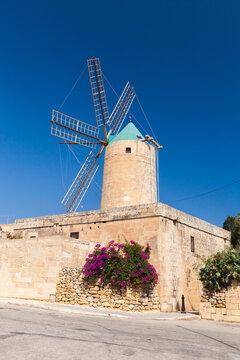 Xaghra Ggantija street view with old windmill under blue sky