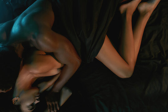 You are my everything. Young sensual african couple of lovers relaxing after amazing sex, they sleeping together on the silk black sheet in bedroom