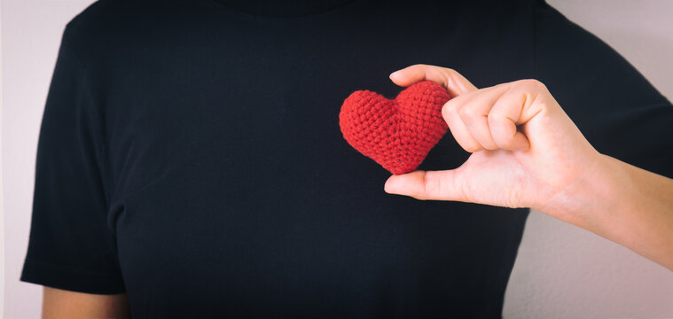 Hands holding red heart on black isolated background, copy space, concept of love, hope,healthcare,organ donation,insurance and CSR, World heart day, National Organ Donor day,World mental heath day.
