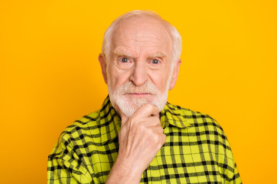 Photo of aged man pensioner angry serious hand touch chin think minded isolated over yellow color background