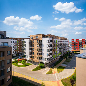 Multi-family building, aerial view. Viaw of block of flats in suburban area under the blue sky with idyllic clouds.