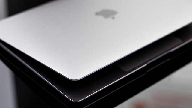 Apple MacBook Air 13 Laptop on glossy black table and blurred background. Close-up, dark tone. Gomel Belarus - 16.02.2021