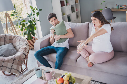 Full length photo of young couple crazy mad woman pregnancy terrified man hold pillow sit sofa inside house indoors