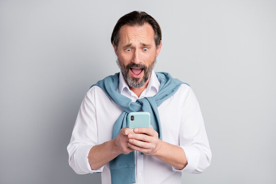 Photo portrait amazed man using app on smartphone reading fake news low battery isolated pastel grey color background