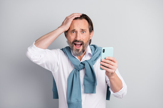 Photo of sad guilty mature guy dressed white shirt pullover shoulders holding modern device arm head isolated grey color background