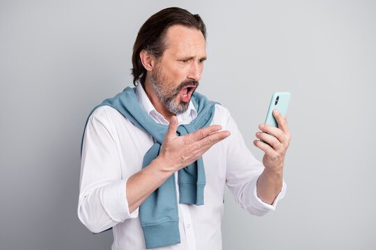 Photo of upset angry mature guy dressed white shirt pullover shoulders looking modern device isolated grey color background