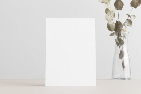 White invitation card mockup with an eucalyptus on a beige table. 5x7 ratio, similar to A6, A5.