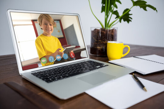 Webcam view of male student on video call on laptop on wooden table